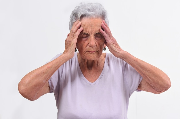 Senior woman with headache on white background