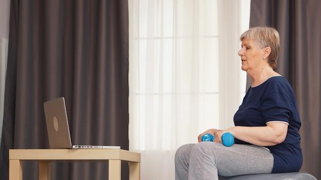 安定ボールにダンベルを使用して健康的なライフスタイルトレーニング腕を持つ年配の女性。オンライントレーニング学習技術老婆リフティングトレーニング健康的なライフスタイルスポーツフィットネストレーニング自宅で