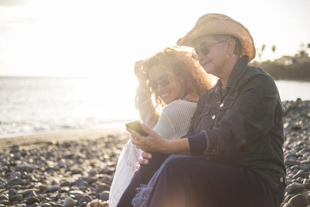 ビーチでリラックスした若い娘と年配の女性。母は娘に携帯電話を見せて笑っている。明るい晴れた日にビーチで彼女の長女とメディアコンテンツを共有する老婆