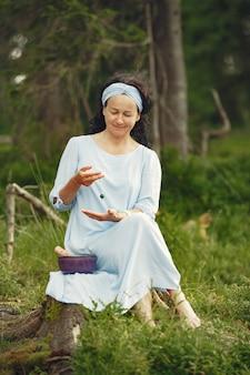 Senior donna con cose indù. signora in un vestito blu. bruna seduta.