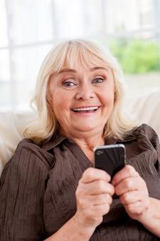 휴대 전화와 함께 수석 여자입니다. 휴대폰을 들고 의자에 앉아 웃고 있는 쾌활한 시니어 여성