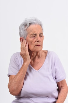 Senior woman with pain on ear on white background