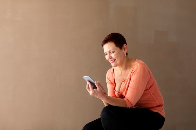 Senior woman with phone smiling