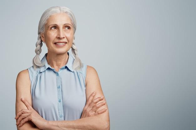 Старшая женщина с косичками, одетая в синюю блузку
