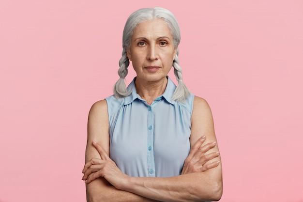 ブルーのブラウスに身を包んだおさげ髪の年配の女性