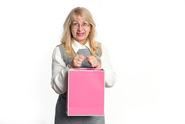 Senior woman with a pink package on a white background.