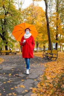 Старшая женщина с защитной медицинской маской на лице гуляет в осеннем парке с оранжевым зонтиком.