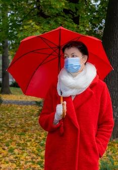 顔にサージカルマスクをかぶった年配の女性が赤い傘を持って秋の公園を散歩します。