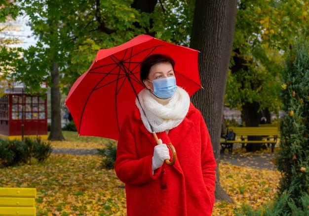 Старшая женщина с защитной медицинской маской на лице гуляет в осеннем парке с красным зонтиком.