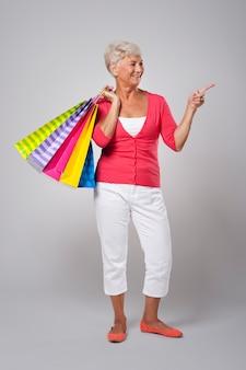 Donna maggiore con i sacchetti della spesa che mostrano sullo spazio della copia