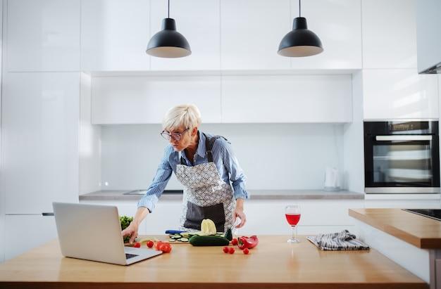 短い髪とエプロンで年配の女性とラップトップのレシピに従い、キッチンに立ちながら食事を準備する