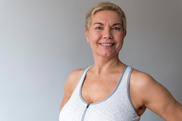Старшая женщина с короткими волосами делает фитнес