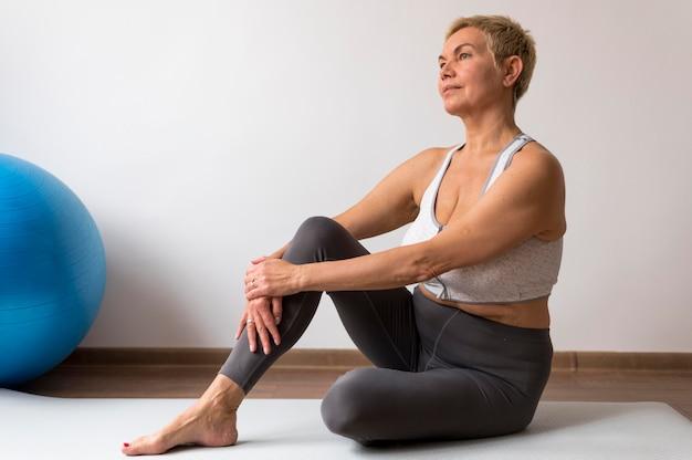 Старшая женщина с короткими волосами делает упражнения на растяжку