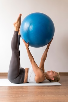 Senior woman with short hair using fitness ball