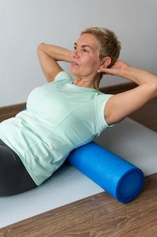 Senior donna con i capelli corti utilizzando un materassino yoga