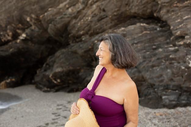 Старшая женщина в соломенной шляпе, наслаждаясь днем на пляже