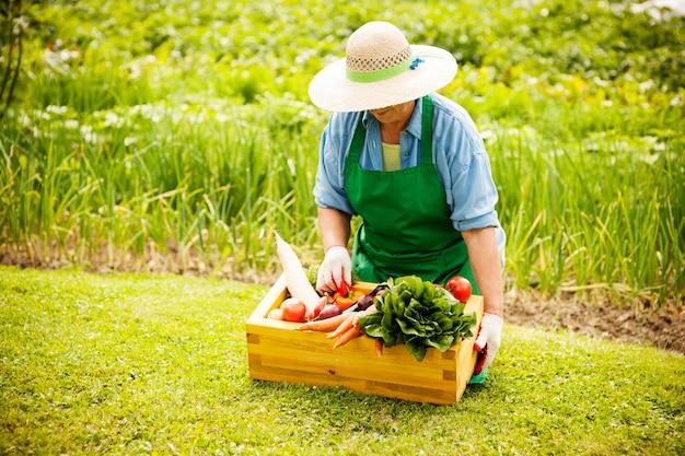 野菜を持つ年配の女性