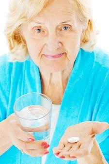 水ガラスと白い背景で隔離のタブレットを持つ年配の女性