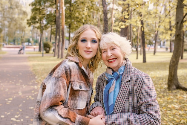 Senior woman with young daughter walking outdoor in autumn park family generation care love