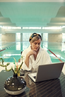 Senior woman working by swimming pool