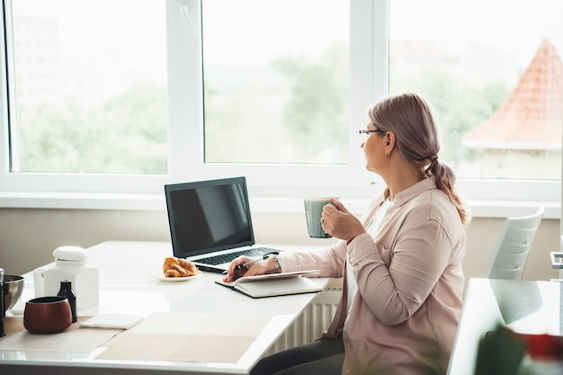 Старшая женщина, работающая из дома во время карантина, смотрит в окно, пьет чай с круассаном и работает за компьютером