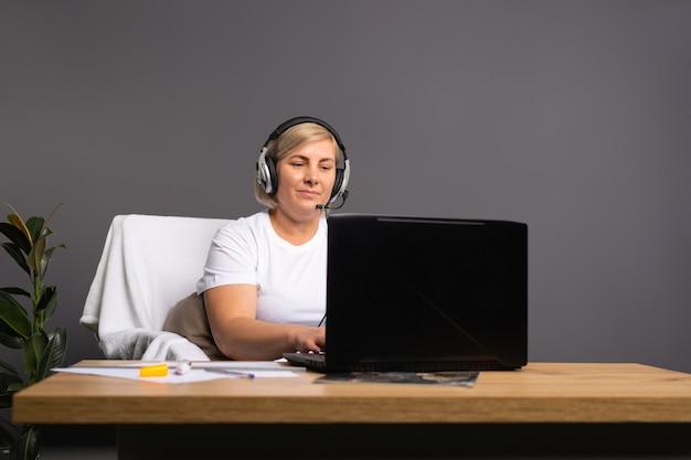 헤드폰에 컴퓨터에서 집으로 일하는 고위 여자
