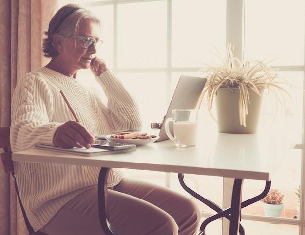 노트북에서 작업 하는 수석 여자. 그녀 옆에 우유 한 잔. 흰색 책상입니다. 창에서 밝은 빛. 새로운 기술을 가진 노인들