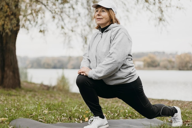 Senior woman working out outdoors on mat