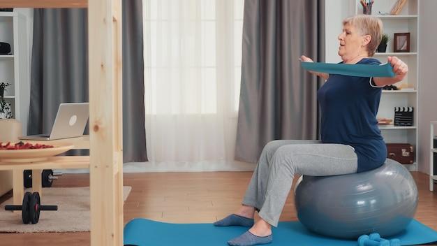 バランスボールとレジスタンスバンドを使って運動する年配の女性。家庭での老人トレーニング健康的なライフスタイル、アパートでの高齢者のフィットネス運動トレーニング、活動とヘルスケア