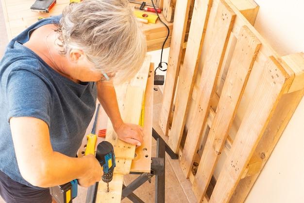 Старшая женщина работает с переработанной древесиной на поддонах, используя множество инструментов и дрели