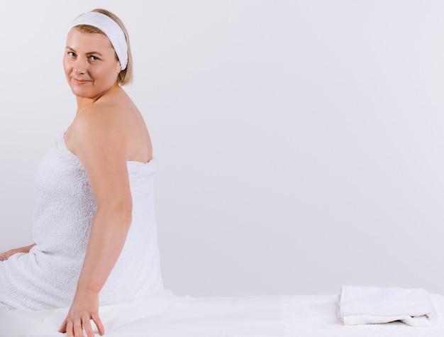 Старшая женщина, завернутая в белое полотенце, сидит на массажном столе перед процедурой и мило смотрит в камеру.