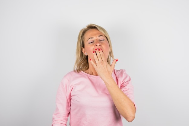 Senior woman yawning in pink blouse