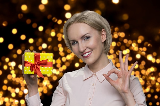 Senior womans holding gift box and showing okay gesture