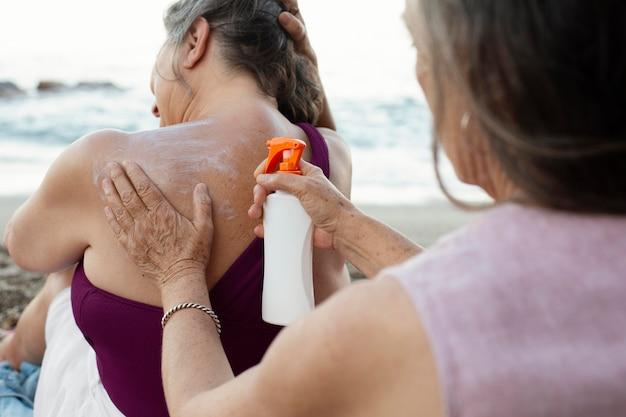 해변에서 뒷면에 자외선 차단제를 적용하는 노인 여성