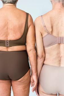 Donne anziane in lingerie marrone e beige ritratto in studio vista posteriore