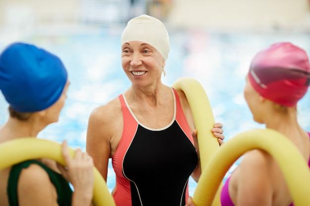 プールでおしゃべりする年配の女性