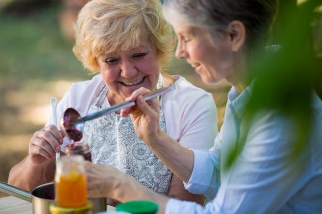 Старшие женщины заполняют варенье в бутылке