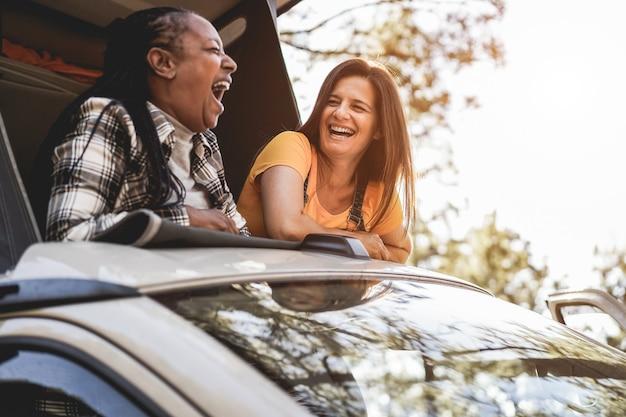 キャンピングカーの中で楽しんでいる年配の女性の友人-右の女性の顔に焦点を当てる
