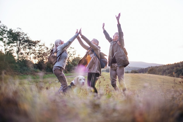 Senior women friends with dog on walk outdoors in nature, jumping.