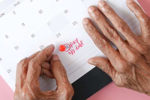 Senior women hand on calendar pointing pay off debt text