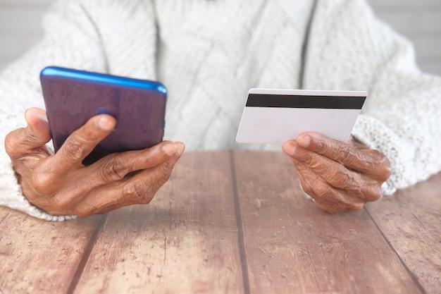 年配の女性がクレジットカードを持ってオンラインショッピングでスマートフォンを使用している