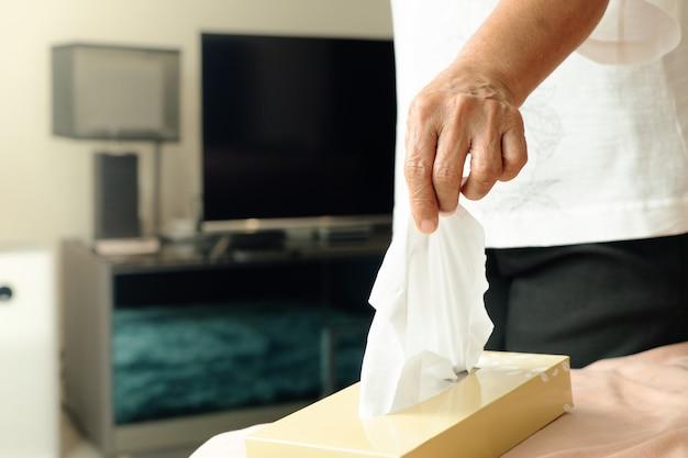 Старшие женщины рука собирают салфетку / папиросную бумагу из коробки для салфеток