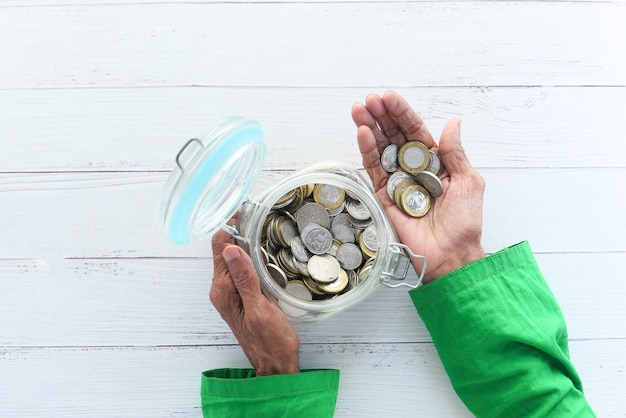 Senior women hand saving coins in a jar, top down ,