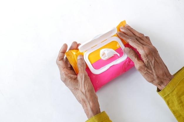 Старшие женщины рука, используя очищающие влажные салфетки на белом фоне