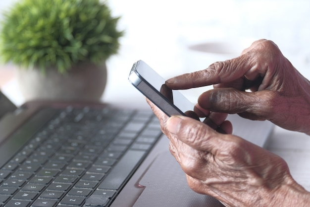 Старшие женщины рука с помощью смарт-телефона крупным планом.