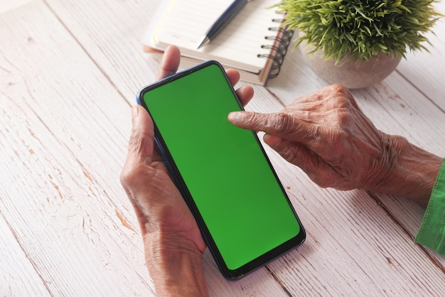 Старшие женщины рука с помощью смартфона крупным планом