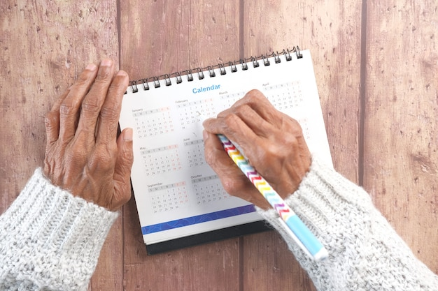 나무 벽에 2021 달력 날짜에 펜 동그라미와 고위 여자 손