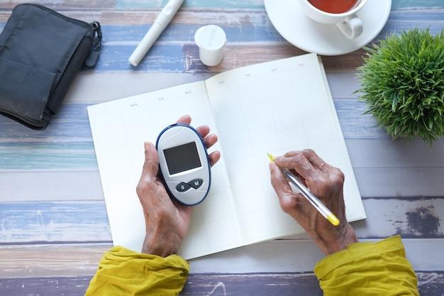 血糖値計を持ってプランナーに書いている年配の女性、