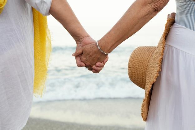 Donne anziane che si tengono per mano in spiaggia