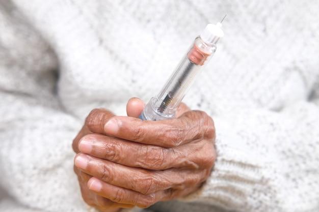 Старшие женщины, держащие инсулиновую ручку крупным планом